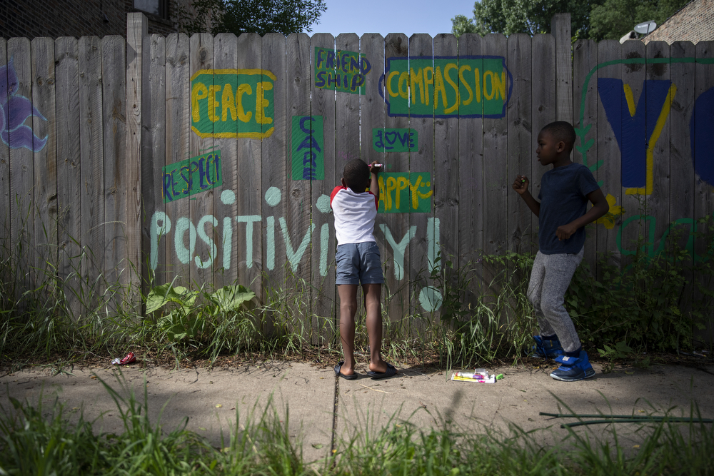 "Rayzell Buick, 6, center, and Camaijah Duff, 6, draw on the fence at the entrance to the Yoga Gardens space Wednesday, June 27, 2018, in the Lawndale neighborhood of Chicago. Buick, who lives across the street, helps out founder Indigo Monae on an almost daily basis. ""Like, some of their parents won't let them outside of the house,"" said Monae, because of some of the violence that often plagues Lawndale. ""Can you image being 6 or 7 years old, you can't go out of the house, you're just in the house all day? They come in here and they just feel like, 'whoa.' They had a good day, they got move around, and their parents are ok with that because then they go to sleep. And then when the veggies grow, they leave here with veggies to give to their parents. So it's like, it's a nice place for them to come and relax."" (Erin Hooley/Chicago Tribune)"