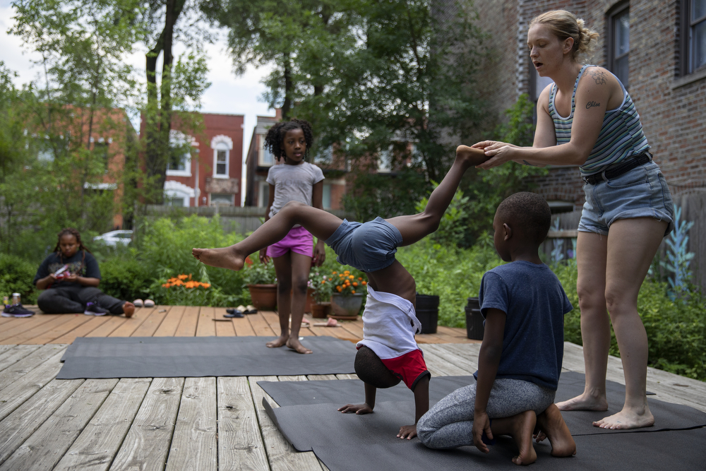 "Volunteer Charlie Renison helps Rayzell Buick, 6, do a headstand during yoga class at the Yoga Gardens space Wednesday, June 27, 2018, in the Lawndale neighborhood of Chicago. Renison has been helping out in the gardens for five years. ""The volunteers that come in here, they love it,"" said Indigo Monae, who has many friends in the Chicago yoga community who regularly help out. ""Like, the kids love it, they want hugs, they remember them by name. That's why I like volunteers who can continuously come, because then like...a lot of people come into these kids' lives and they just disappear. So, a volunteer like Charlie who can be here for a few years, is really good, because then they develop a connection, they develop a love, they feel safe, and they can talk to us."" (Erin Hooley/Chicago Tribune)"