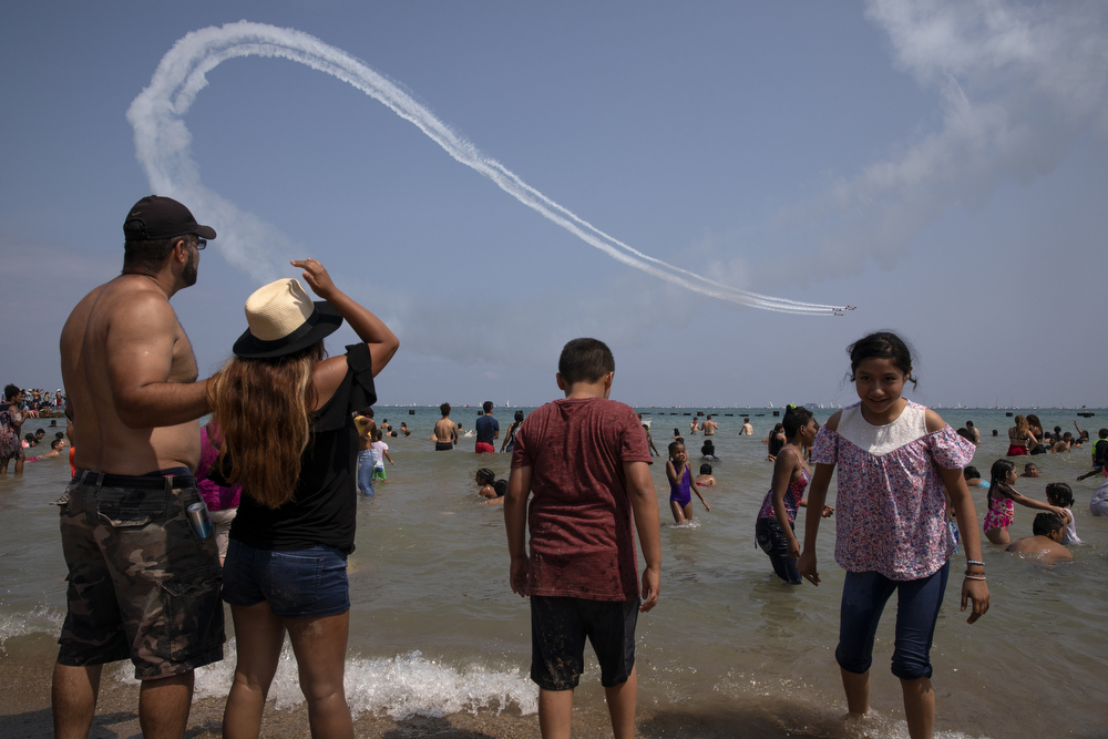 Spectators watch as the AeroShell Aerobatic Team performs during the Chicago Air and Water Show at North Avenue Beach Sunday, Aug. 19, 2018, in Chicago. (Erin Hooley/Chicago Tribune)
