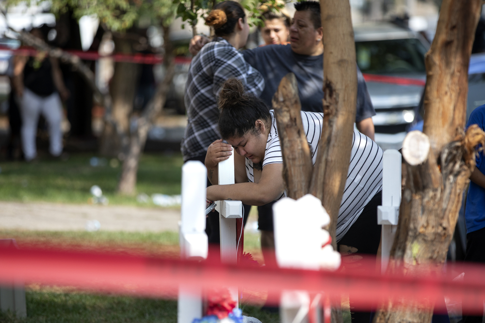 A woman hugs a wooden cross at the scene of a fire that killed at least 8 people, including 6 children, in the 2200 block of South Sacramento Avenue Sunday, Aug. 26, 2018, in the Little Village neighborhood of Chicago. (Erin Hooley/Chicago Tribune)