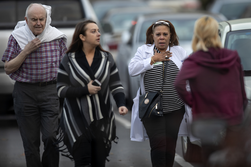 "People walk through the parking lot as they evacuate Mercy Hospital & Medical Center during an active shooter attack that left four people dead, including Chicago police Officer Samuel Jimenez, Monday, Nov. 19, 2018, in the Bronzeville neighborhood of Chicago. The shooter, Juan Lopez, 32, confronted emergency room doctor Tamara O'Neal, apparently over a ""broken engagement,"" killing her, 24-year-old first-year pharmacy resident Dayna Less, and Officer Jimenez, who responded to the shooting. Lopez was found inside dead the hospital, apparently suffering a wound to the head, but it was unclear how he was shot. (Erin Hooley/Chicago Tribune)"