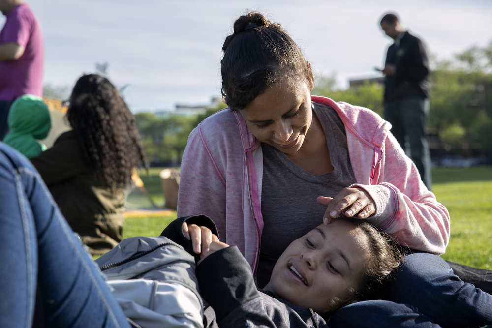 16-year-old Mariana Portillo Flores lays in the lap of her mother Maritza Flores at Dunbar Park Wednesday, May 23, 2018, in Chicago. The Flores family left their home country of El Salvador years ago due to gang violence, living in Guatemala for awhile before ending up in Mexico. They crossed the border into the United States as part of a caravan of hundreds of people, organized by Pueblo Sin Frontreras, where they surrendered and sought asylum. Pueblo Sin Frontreras worked with Showing Up for Racial Justice, a national network of activists, to find sponsor families, like the DeMay-Gres family in Chicago, to house those in the caravan who did not have relatives in the United States. (Erin Hooley/Chicago Tribune)
