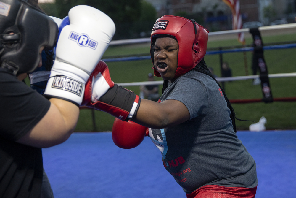 13-year-old Tyesha Steen of Franklin Boxing, right, spars with 28-year-old Charise Horn of Unanimous Boxing Gym at a women's-only boxing exhibition event Thursday, May 30, 2019, at Eckhart Park in Chicago. (Erin Hooley/Chicago Tribune)