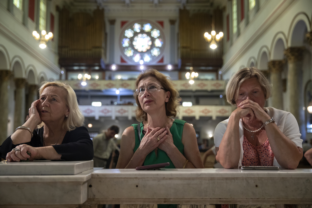 "From left, Jadzia, Lucy Smagacz and Barbara Radlinska kneel at the altar at what may be the final mass held at St. Adalbert's Catholic Church Sunday, July 14, 2019, in the Pilsen neighborhood of Chicago. A decree from the Archdiocese of Chicago declared the last mass was to take place on July 14. In a press release, the St. Adalbert Preservation Society stated that although a petition to keep the church open was ""rejected by the Cardinal and the officers of the Archdiocese of Chicago in a letter and decree dated July 8, 2019,"" it will now take the petition to the Vatican. (Erin Hooley/Chicago Tribune)"