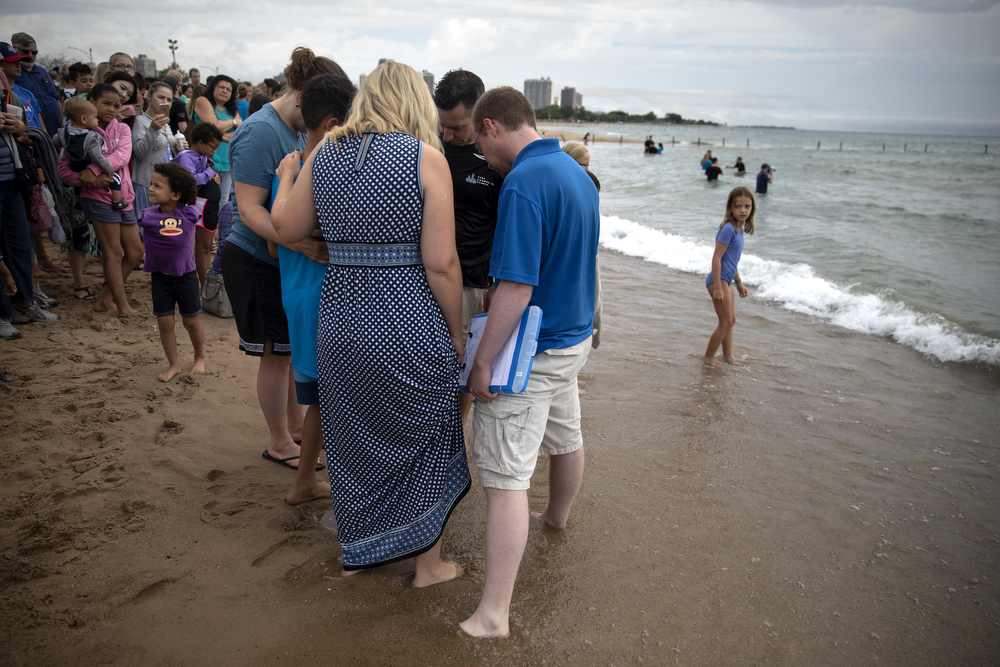 A group of people with Park Community Church pray together as others are baptized in the waters of Lake Michigan at North Avenue Beach Sunday, July 21, 2019, in Chicago. (Erin Hooley/Chicago Tribune)