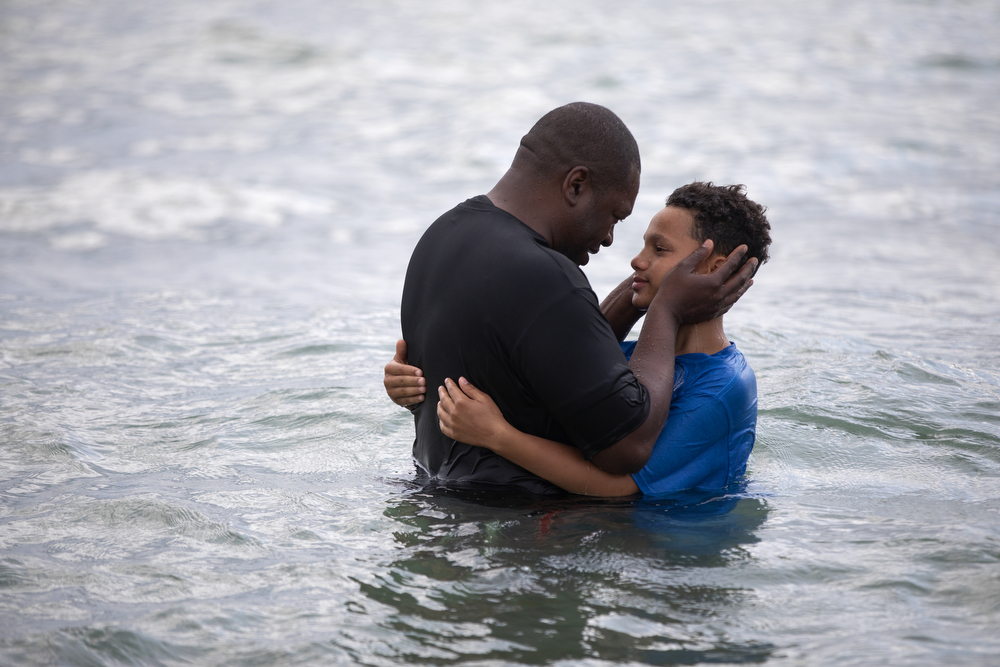 12-year-old Andrew Payne gets a huge from his father, Park Community Church Pastor Nathan Payne, after being baptized in the waters of Lake Michigan at North Avenue Beach Sunday, July 21, 2019, in Chicago. (Erin Hooley/Chicago Tribune)