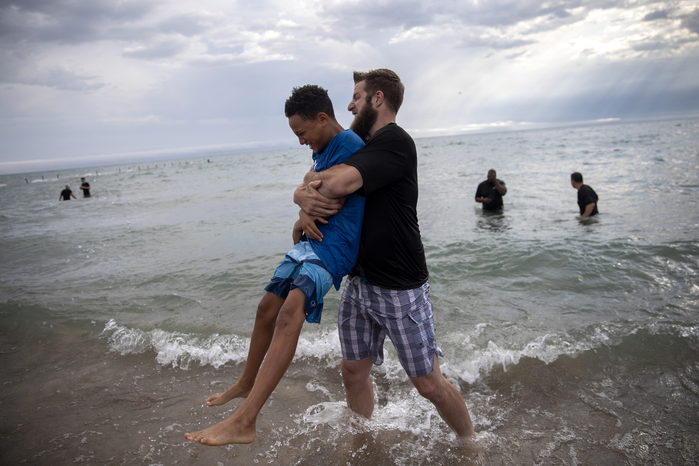12-year-old Andrew Payne gets a hug from Park Community Church Student Ministry Director David Paukovitz after being baptized in the waters of Lake Michigan at North Avenue Beach Sunday, July 21, 2019, in Chicago. (Erin Hooley/Chicago Tribune)