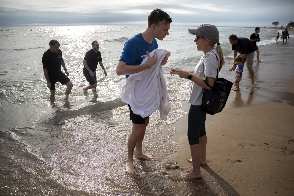 Spencer Tiedge gets a towel from fiancee Hattie Hoskins after he was baptized in the waters of Lake Michigan at North Avenue Beach Sunday, July 21, 2019, in Chicago. (Erin Hooley/Chicago Tribune)