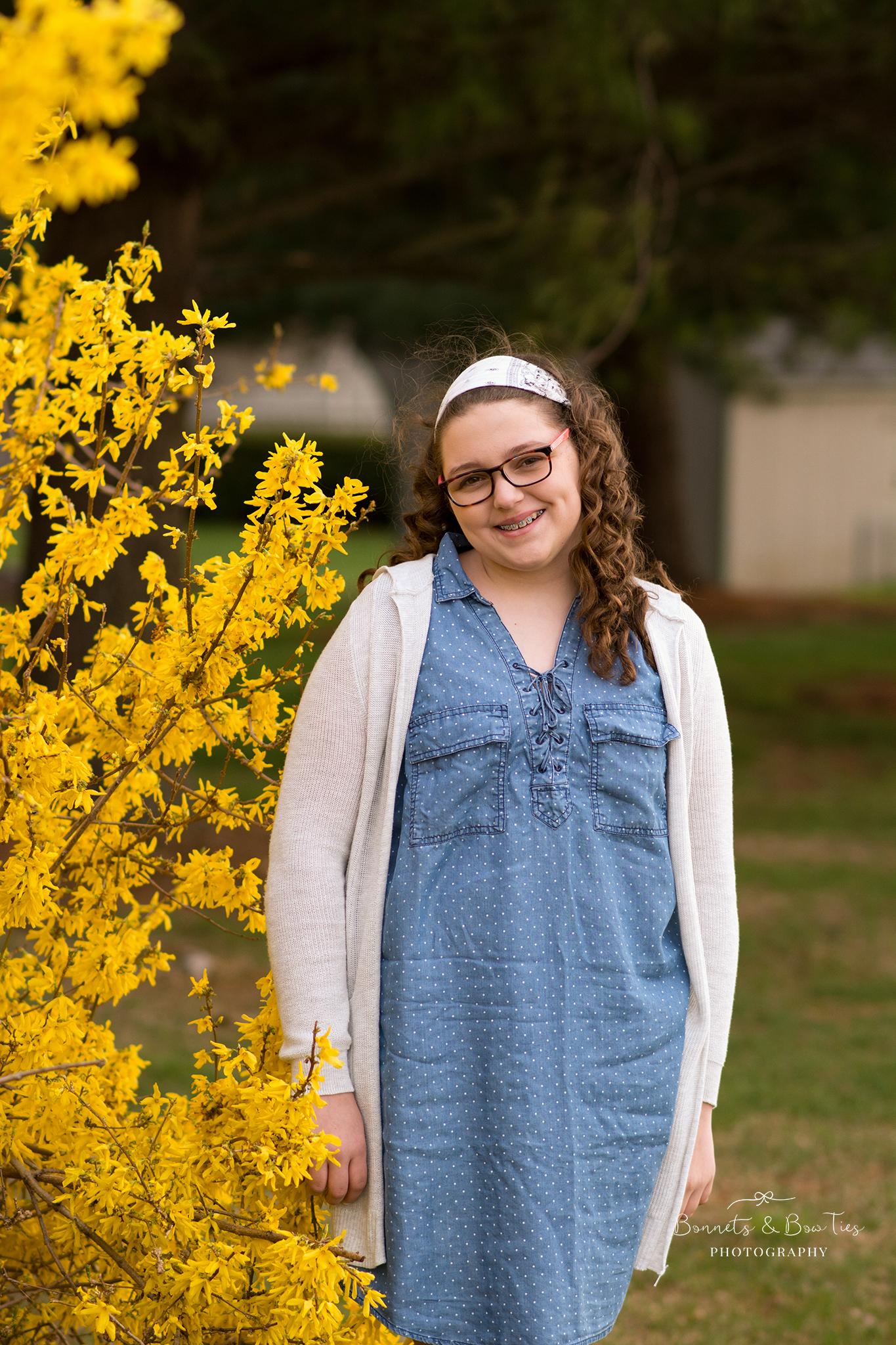 girl wearing blue against yellow flowers.jpg