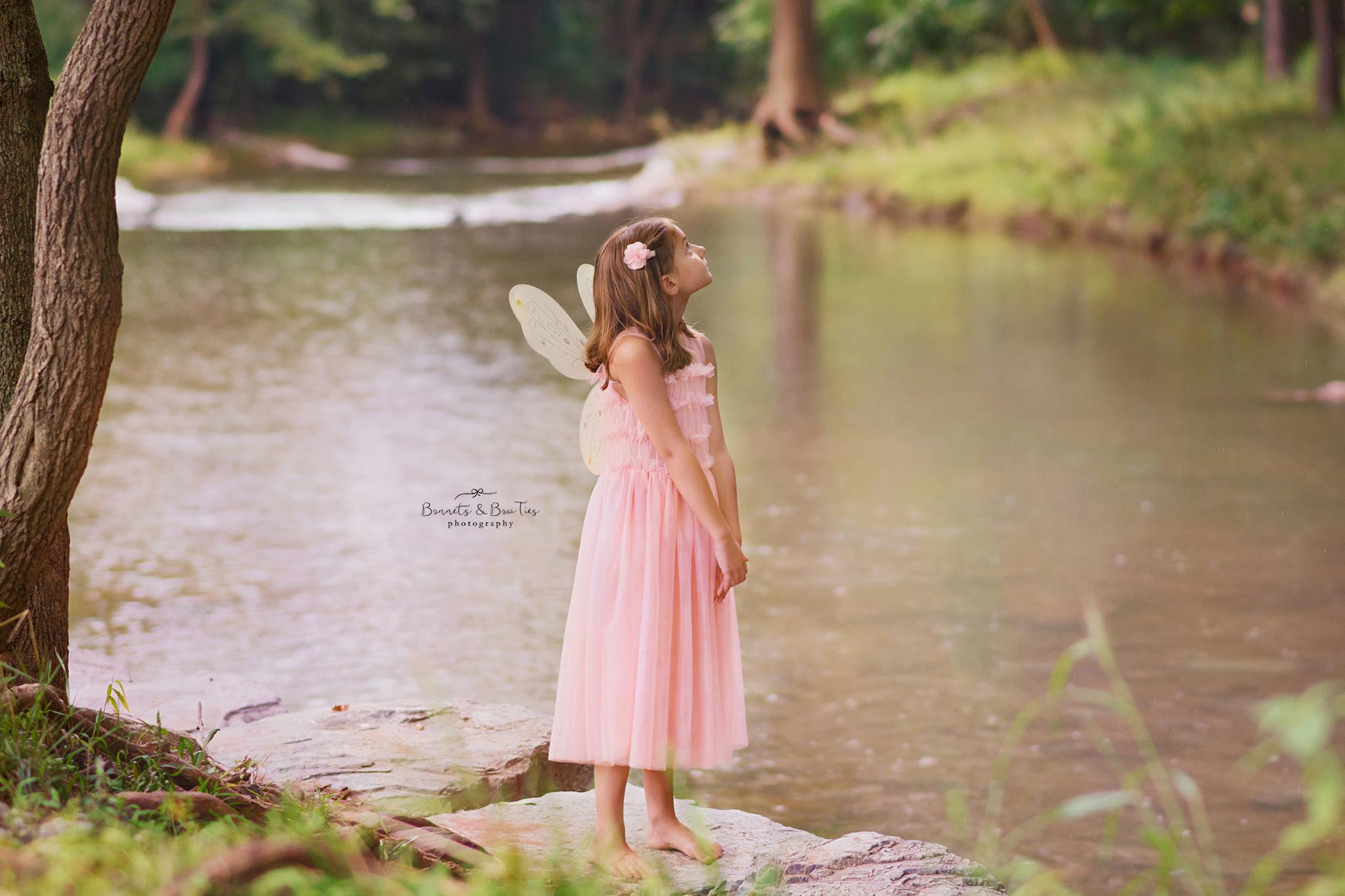 little girl in pink dress in creek.jpg