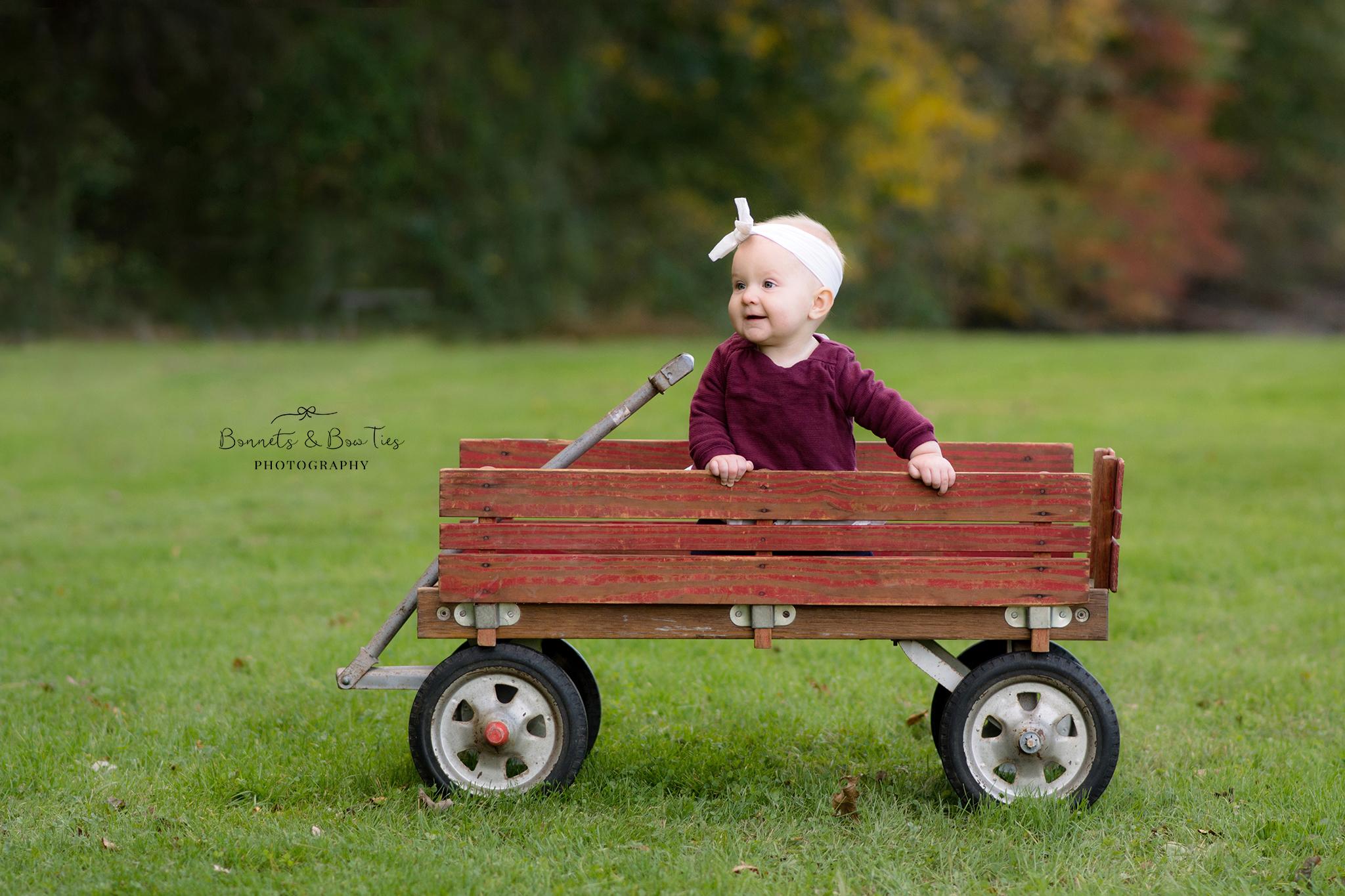baby girl sitting in a wagon.jpg