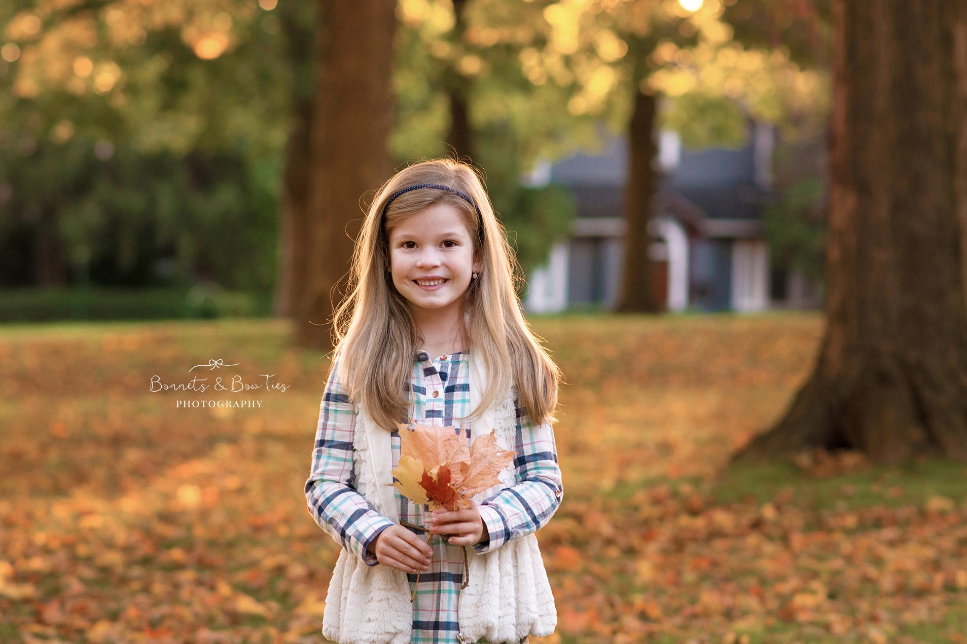 girl poses holding leaf.jpg