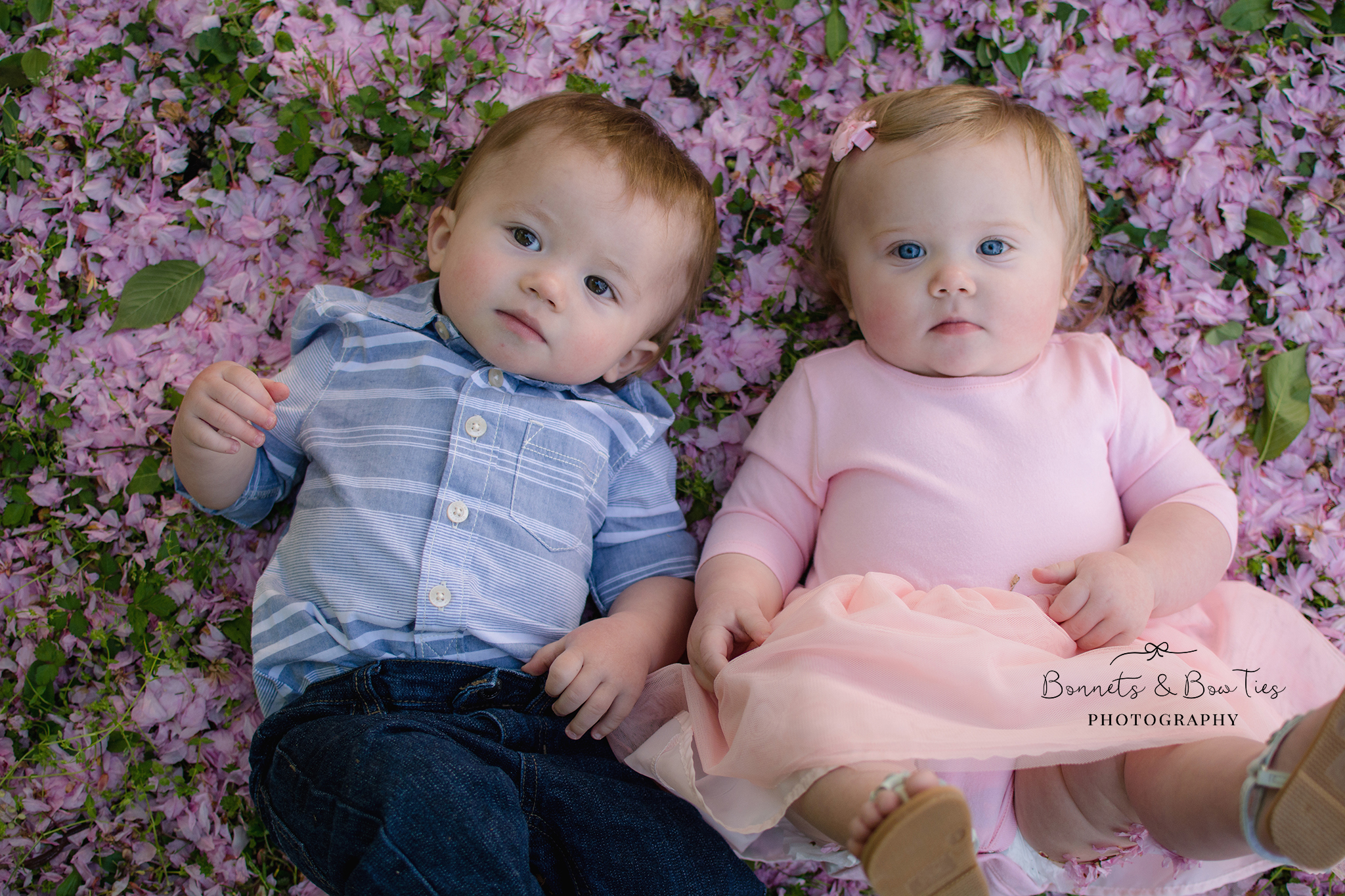 boy and girl twins laying on pink petals.jpg