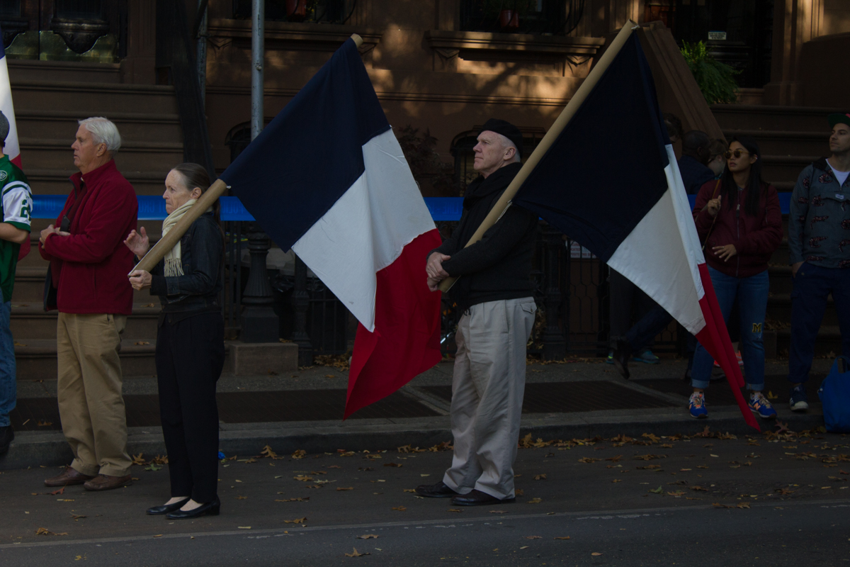 Two people with French flags stand ready to cheer on cyclists and runners in Brooklyn.