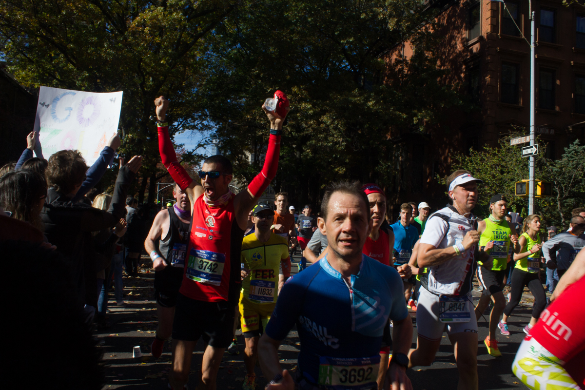 A marathoner cheers back at the crowd.