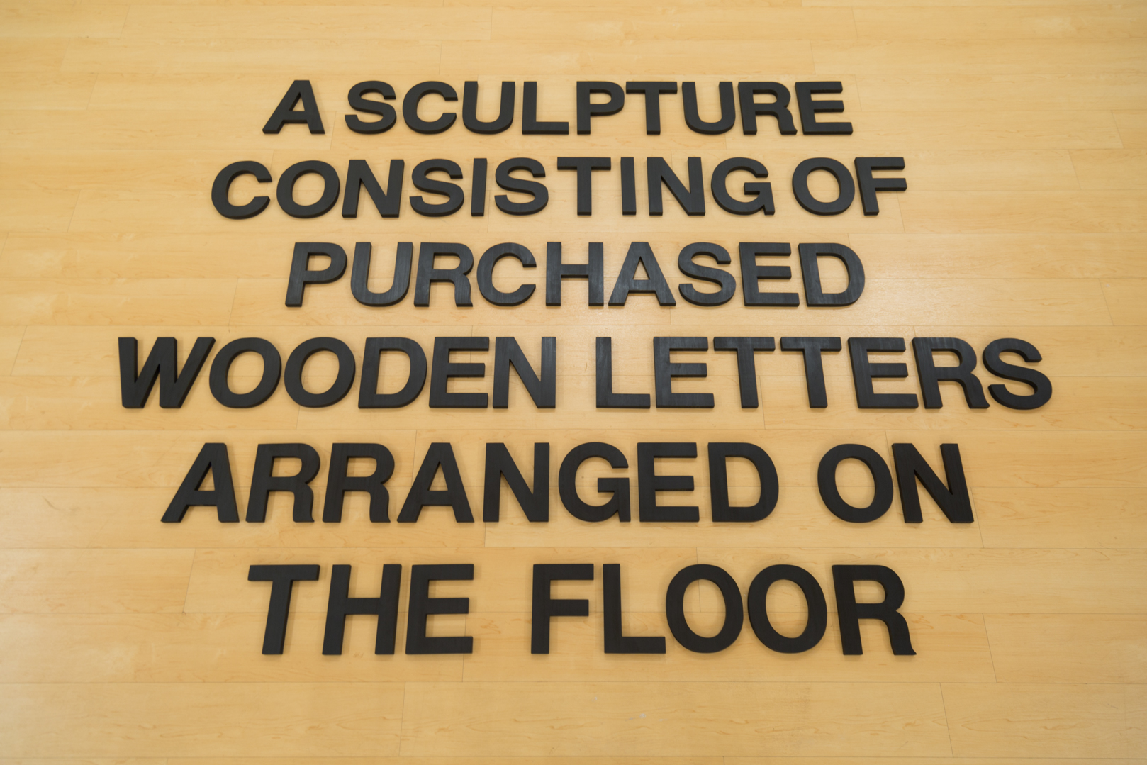 A Sculpture Consisting of Purchased Wooden Letters Arranged on the Floor , 2019  Wood, India ink, and wax Size variable