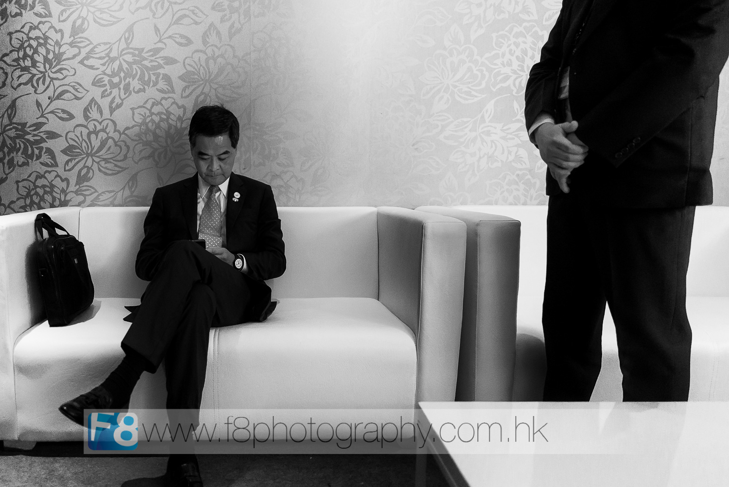 chief executive of hong kong, mr cy leung checks his speech notes before going on stage in front of thousands of ceo's and vvip guests at apec 2015.  his bodyguard stands close by.