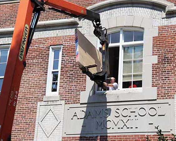 Sheetrock for the blackboard project is hoisted in through the math office window.