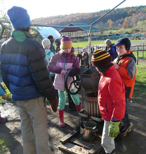 Students enjoyed taking turns pressing apple cider.