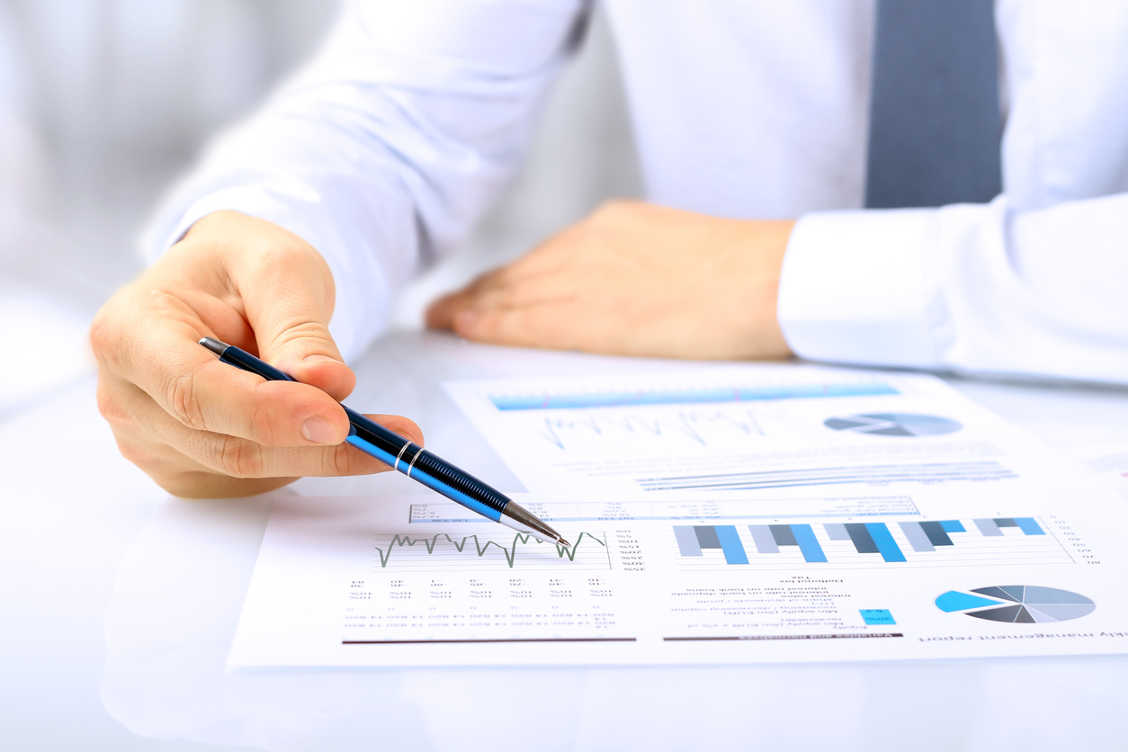 A businessman reviews forecasts on paper with pen