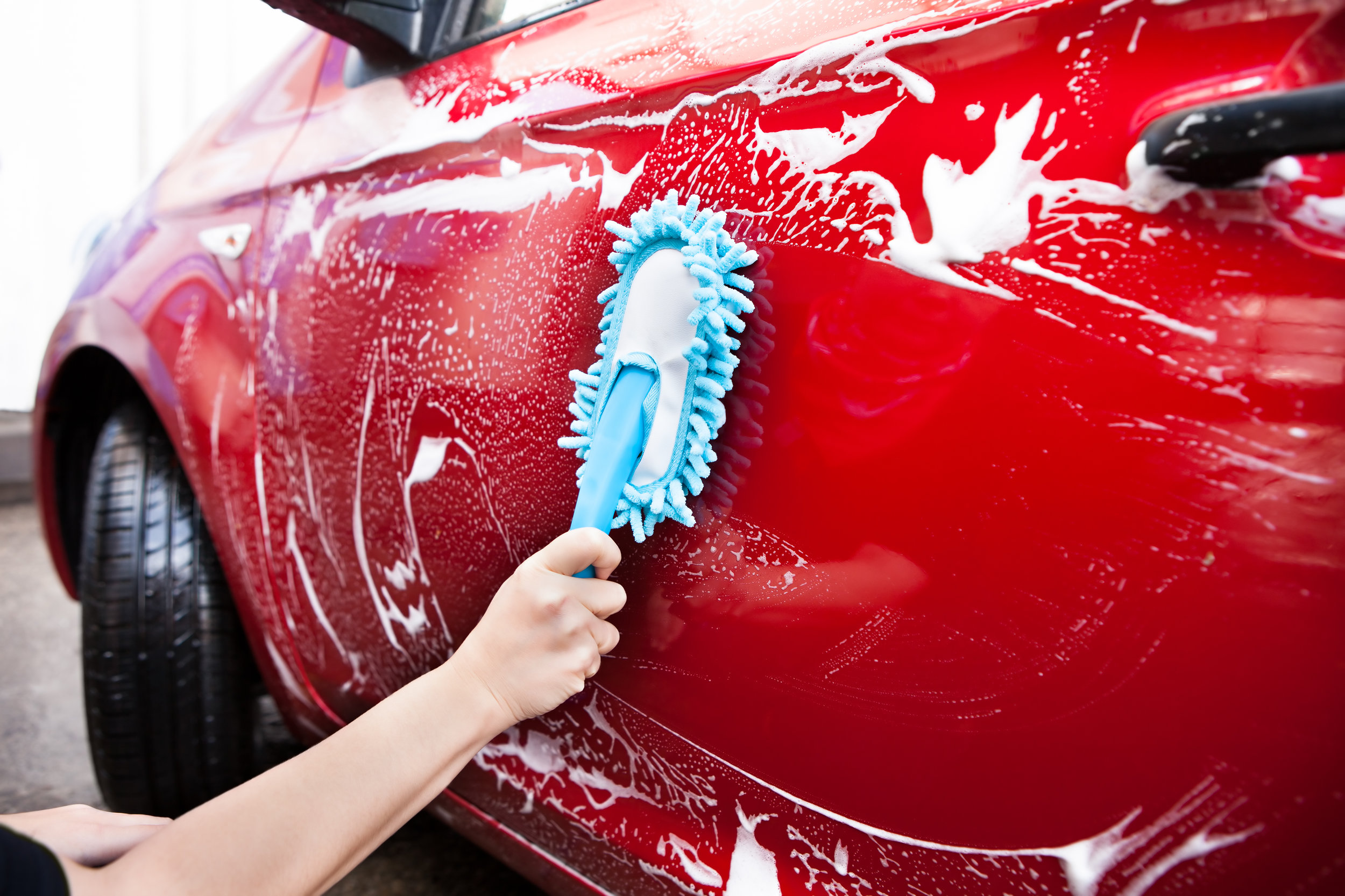 A hand washing a car with a brush