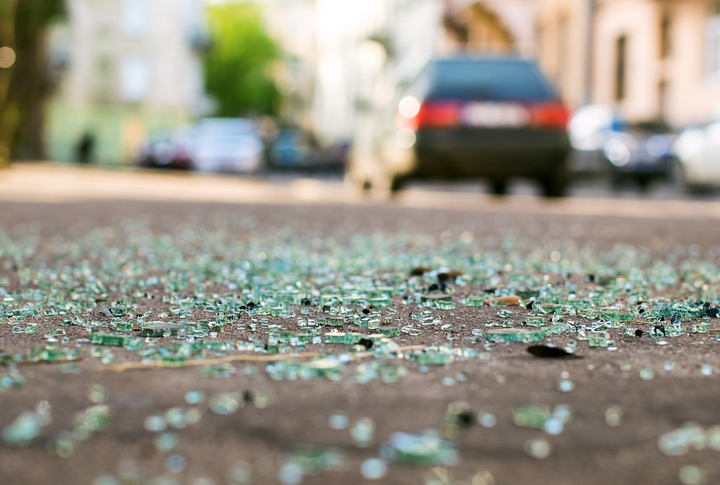 Close-up image of broken glass on the road after a car accident