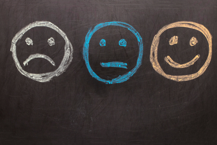 Drawing-Unhappy-and-Happy-Smileys-on-Blackboard.jpg