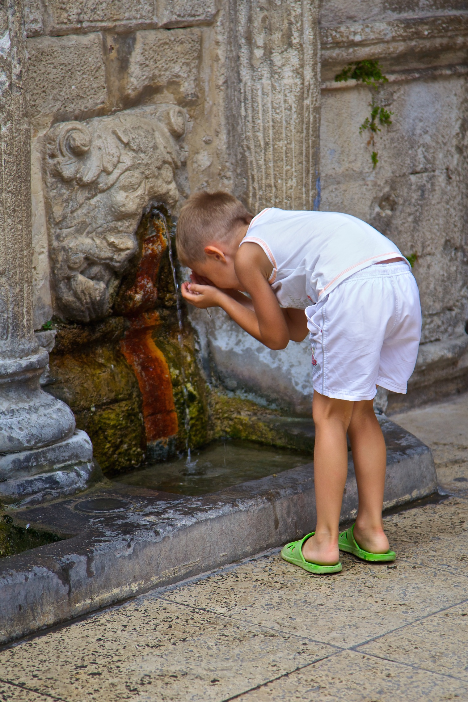 Drinking water from an ancient fountain. Crete, Greece