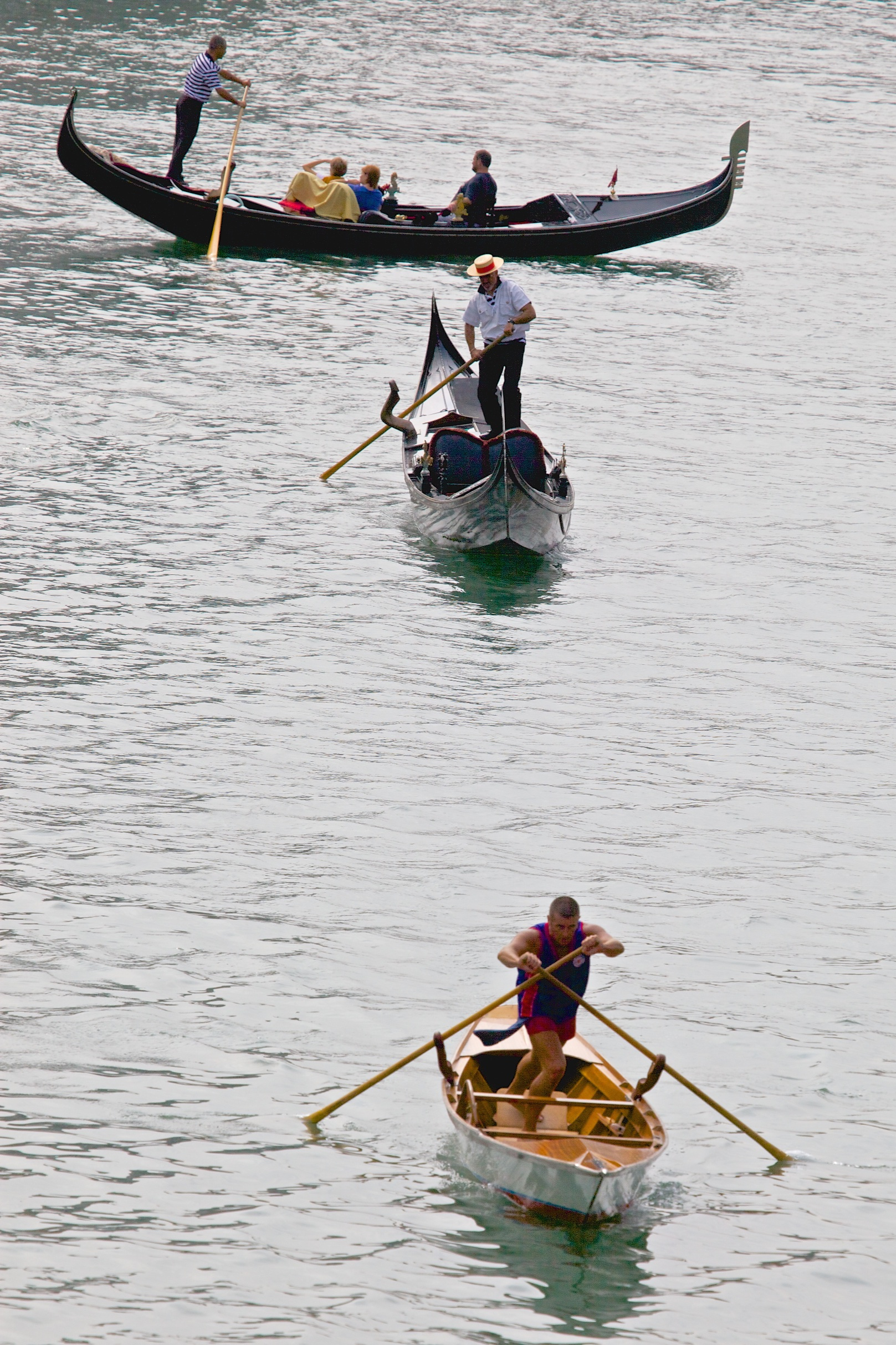 Different rowing techniques crossing the Canale Grande in Venice.