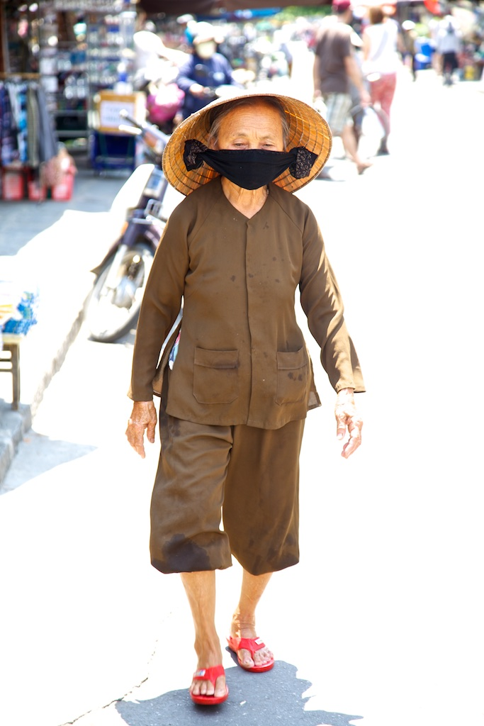 A practical way to simultaneously get protection against the sun and vehicle contamination. Hoi An, Viet Nam