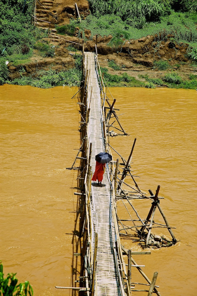 A muddied river bridge crossing. Luang Prabang, Laos.