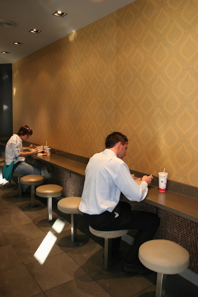 Sharing a long-distance meal facing a wall. McDonalds, Sydney, Australia.