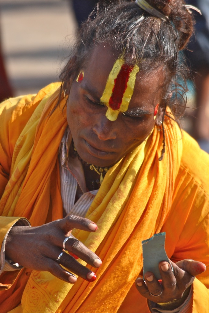 Sadhu makeup with the help of a broken mirror. Orchha, India
