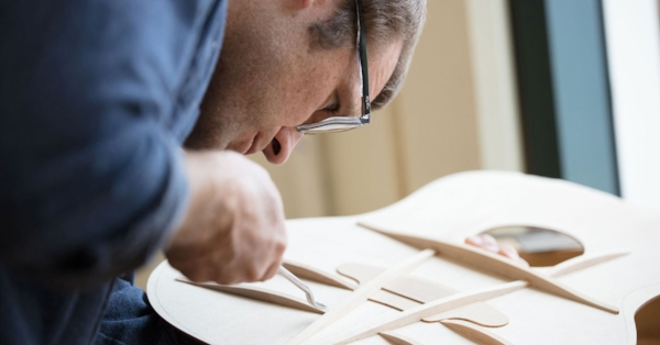Andy Powers refines a V-Class System build. Photo courtesy of Taylor Guitars.