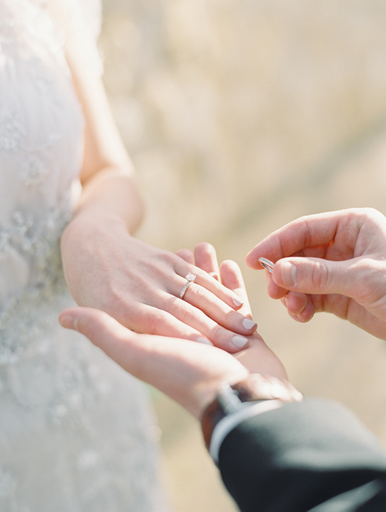 groom putting on bride's ring during the ceremony