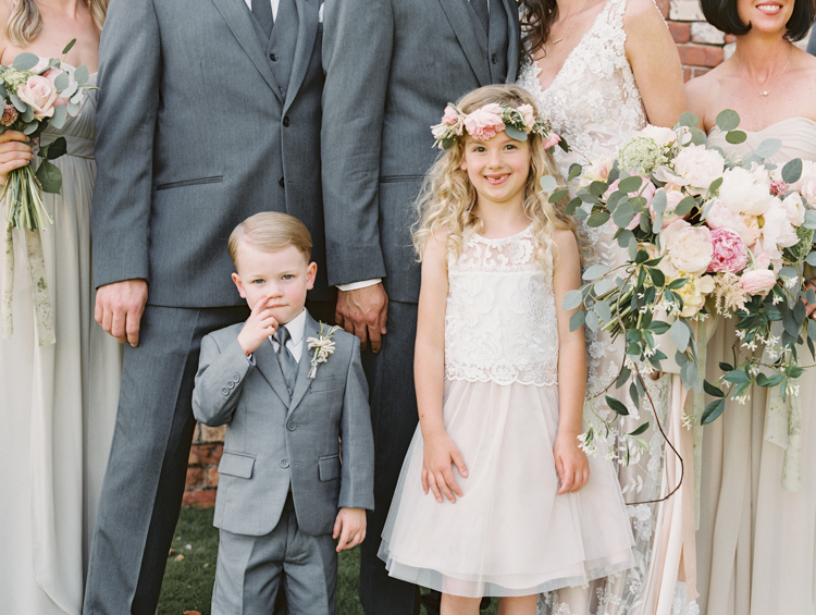 flower girl with flower crown and ring bearer picking nose