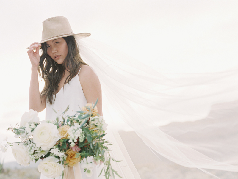 bride wearing cowboy hat and veil desert wedding
