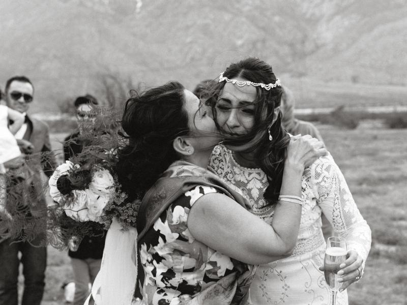 mom kissing bride during wedding