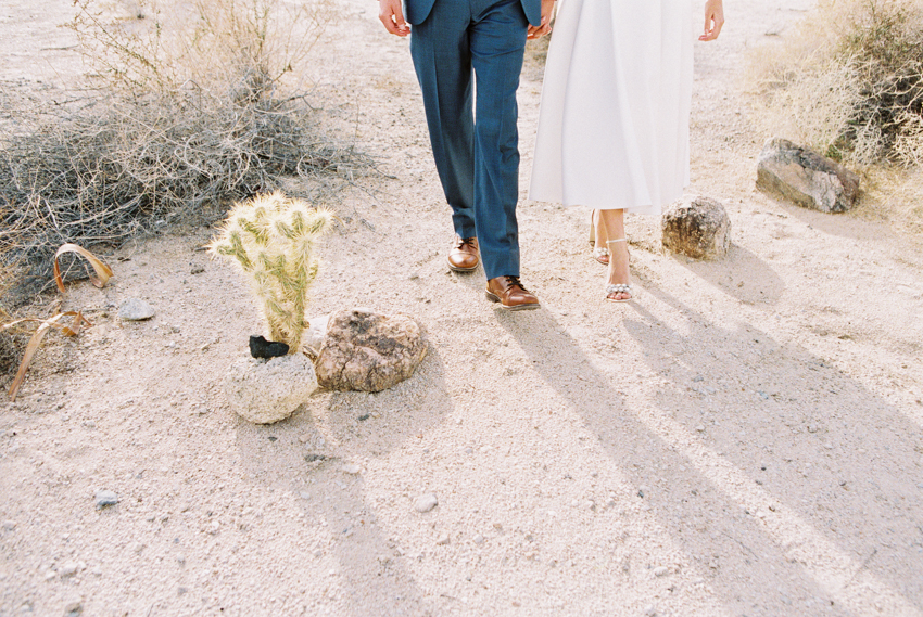 bride and groom walking in the desert