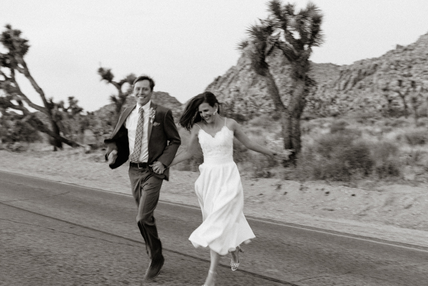 bride and groom running in the street joshua tree national park