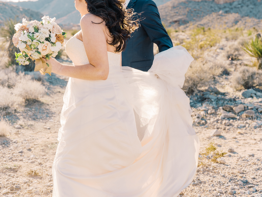 groom holding onto brides dress as their walking through the desert