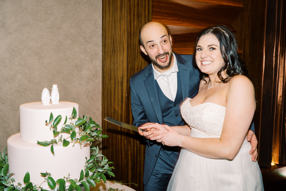 groom surprise expression while cutting wedding cake