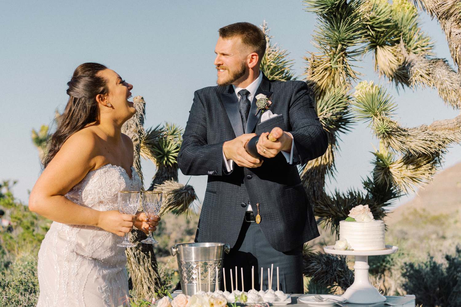 bride and groom popping the champagne outside