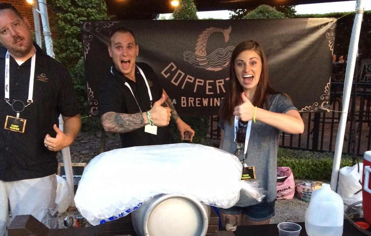 Assistant Brewer, Derrick Gough, and his wife, Erin Gough, serve up beer at a local beer fest while some weird guy crowds into the picture (on the left.)