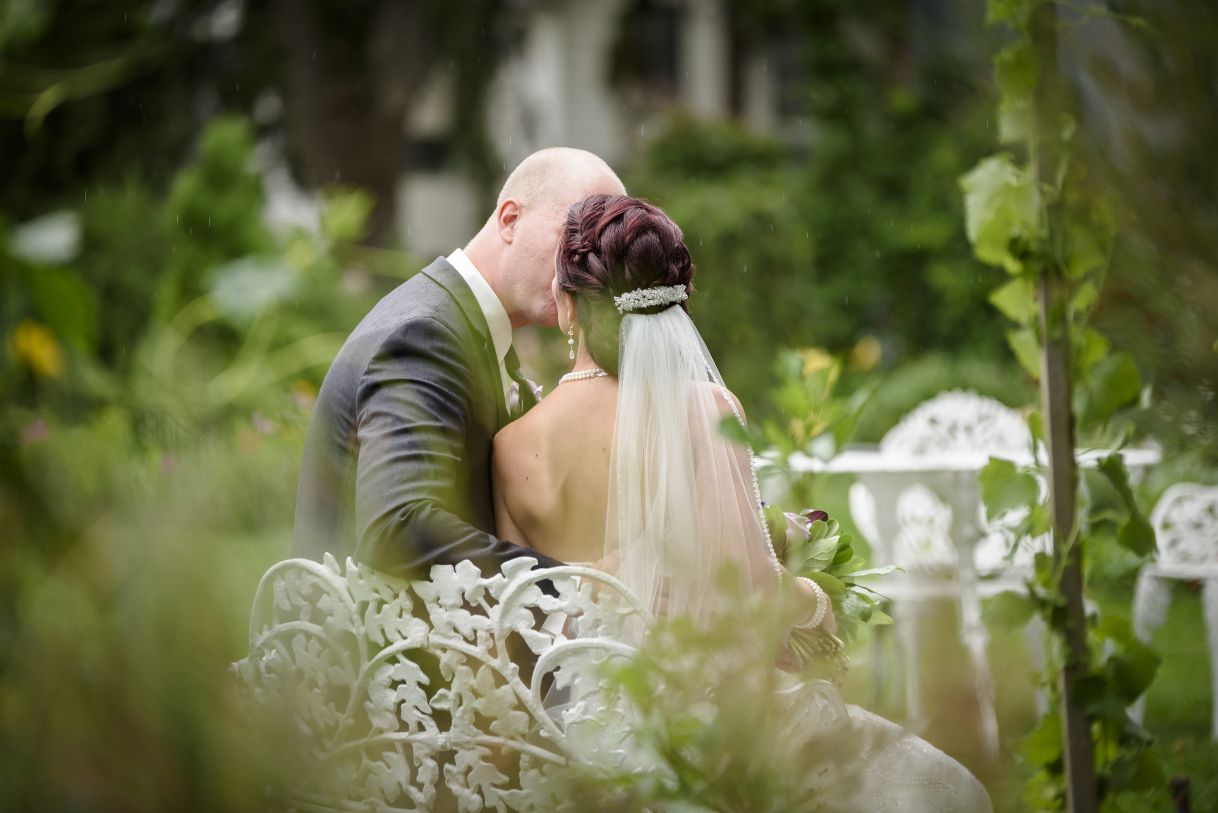 Bride and Groom sitting on a white bench, kissing in the distance