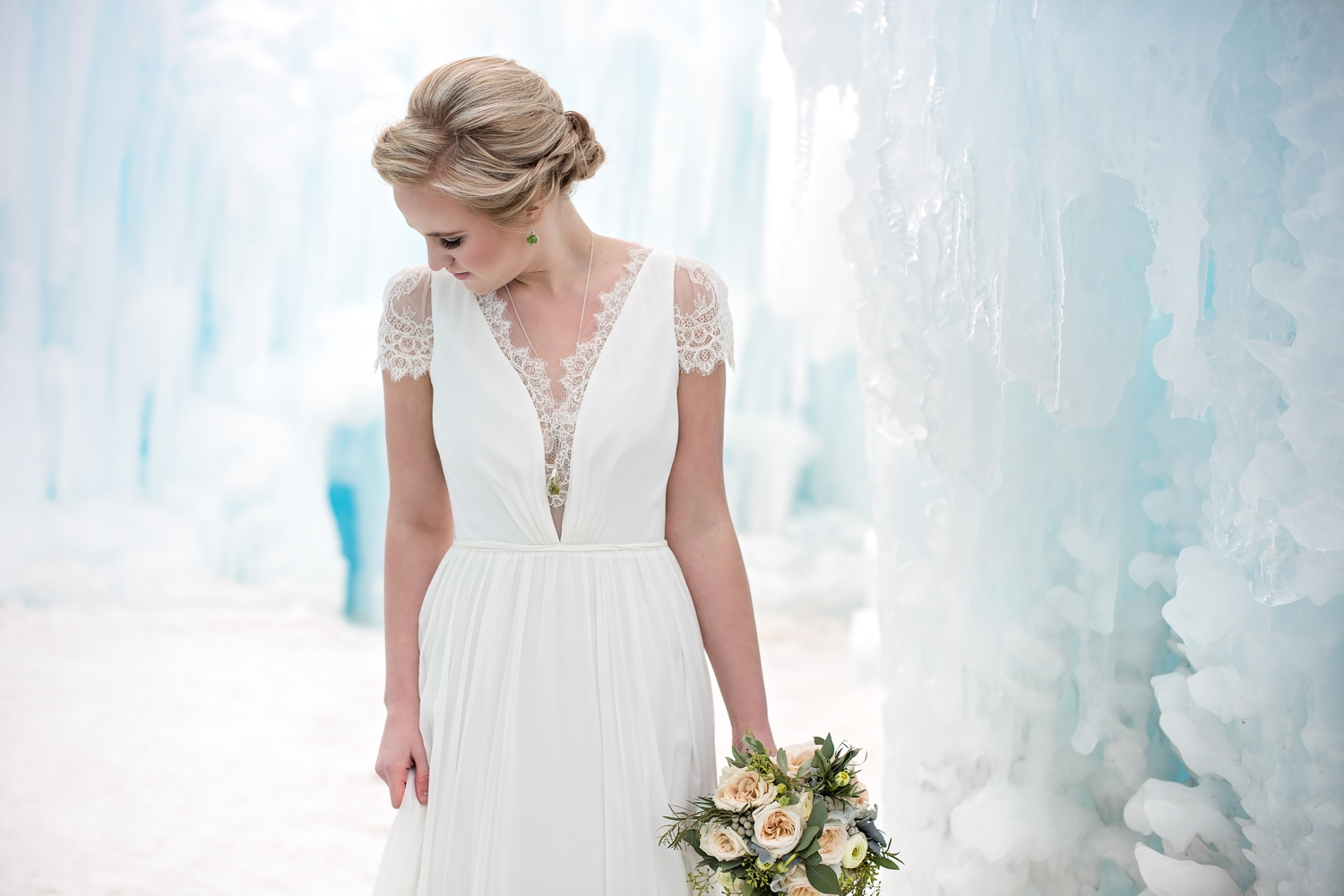 Bride wearing a Christos Bridal wedding dress standing in an ice castle