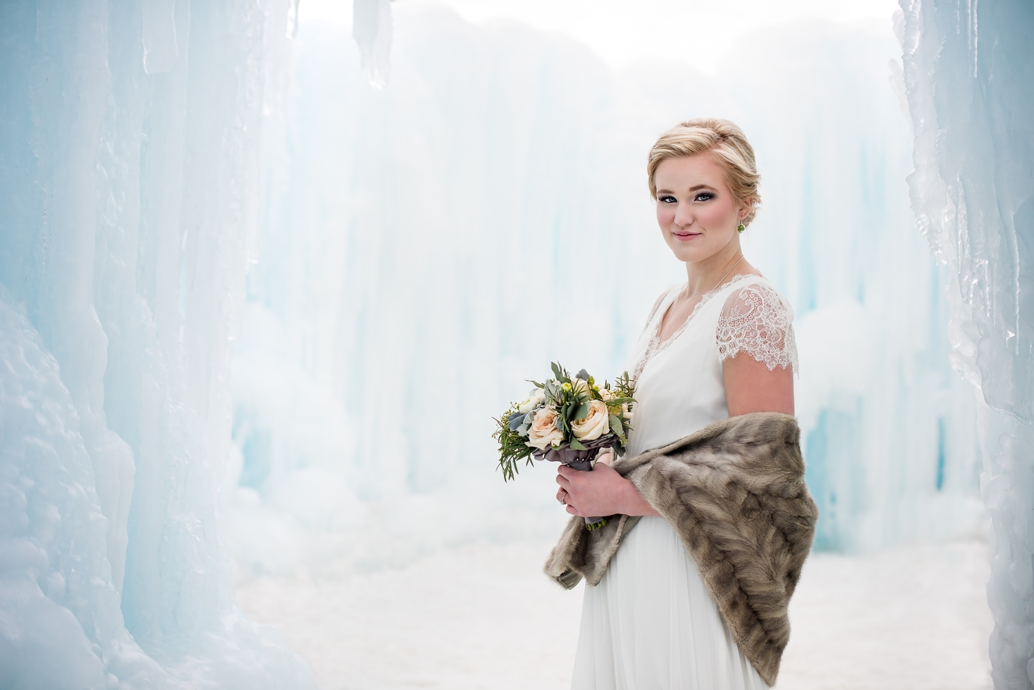 Bride wearing a Christos Bridal wedding dress standing in an ice castle with a fur shawl