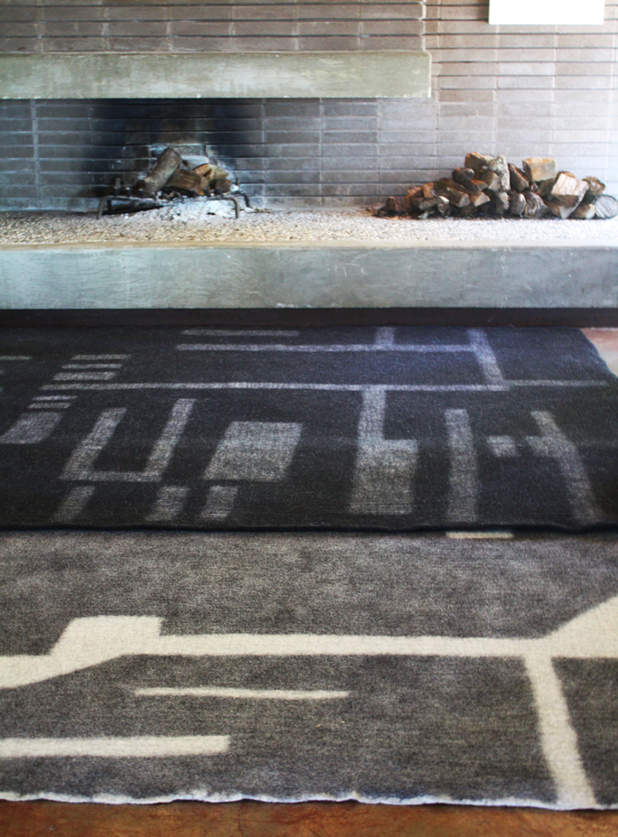 Overlapping Rahita rug and Chacha rug pair unstructured edges with designs resembling abstracted architecture.