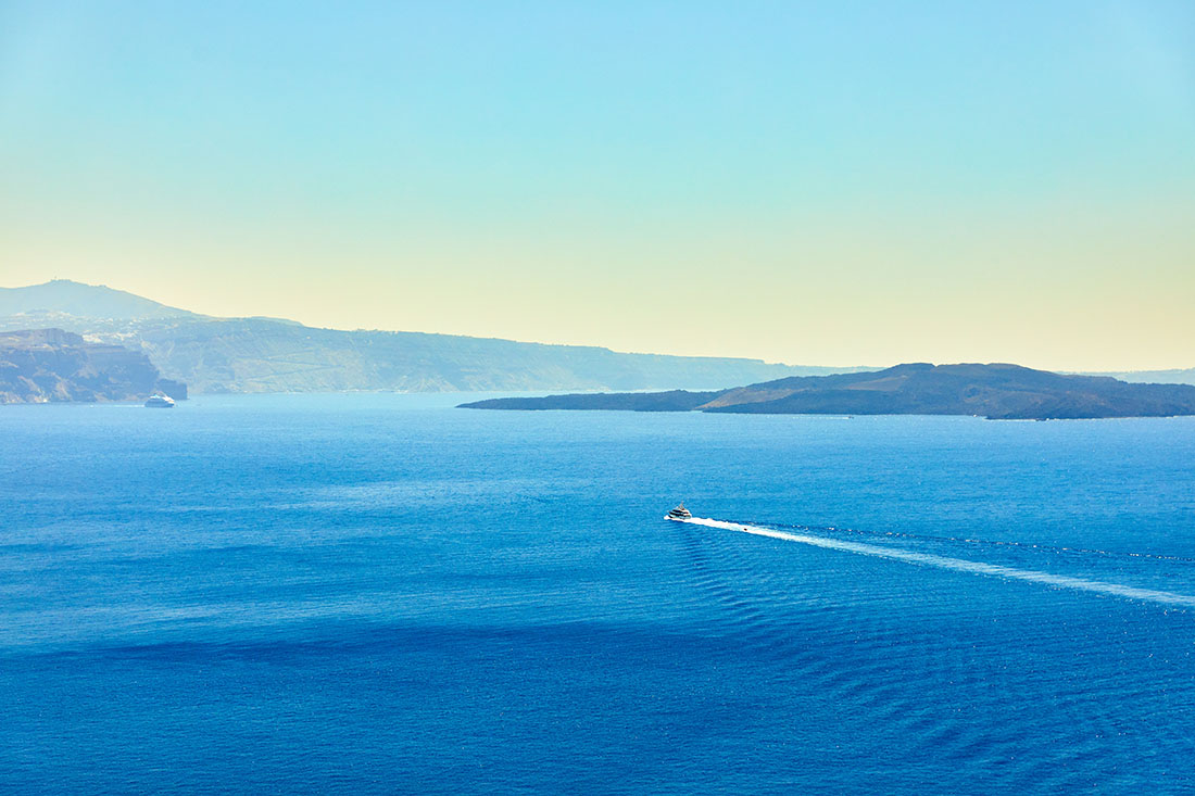 Top view of a white boat sailing in the blue sea
