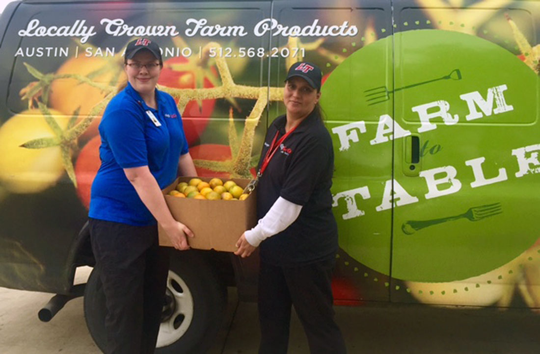 Fuel Café Specialist    Rachel Stewart    (left) and Fuel Café Manager  Tanya Olvera-Breazeale  (right) display a box of farm-fresh, Texas oranges headed to the Lake Travis Middle School cafeteria.